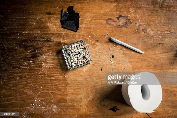 Directly Above Shot Of Cigarette Butts In Ashtray By Tissue Roll On Table