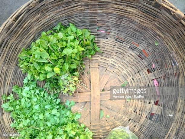 Directly Above Shot Of Cilantro And Mint Leaves For Sale In Basket At Market