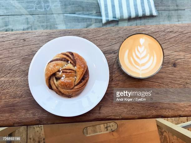 Directly Above Shot Of Cinnamon Bun With Coffee On Wooden Table