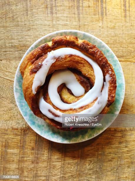 Directly Above Shot Of Cinnamon Bun With Cream In Plate On Wooden Table