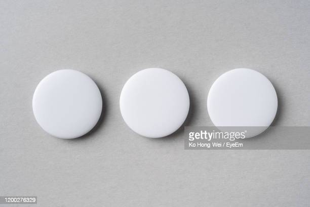 directly above shot of circular badges on gray table - メダル ストックフォトと画像