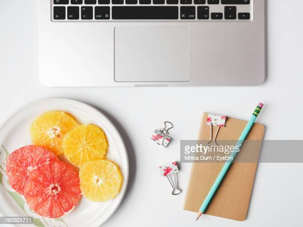 Directly Above Shot Of Citrus Fruit Slices In Plate By Laptop And Diary On Table