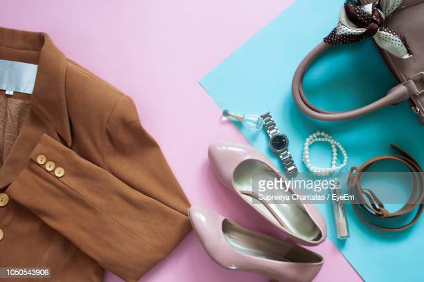 directly above shot of clothing with purse and shoes on table - blue purse stock pictures, royalty-free photos & images