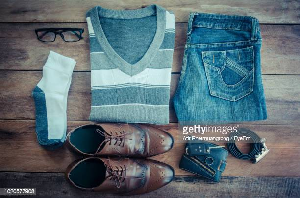 directly above shot of clothing with shoe on hardwood floor - leather belt stock pictures, royalty-free photos & images