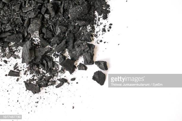 directly above shot of coals on white background - coal stock pictures, royalty-free photos & images