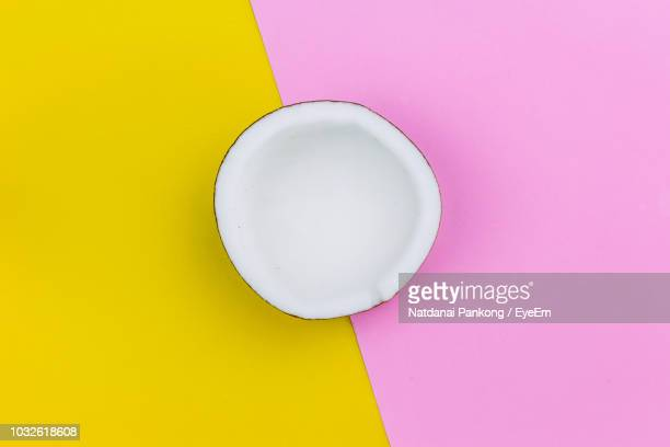 directly above shot of coconut on colored background - coconut stock pictures, royalty-free photos & images