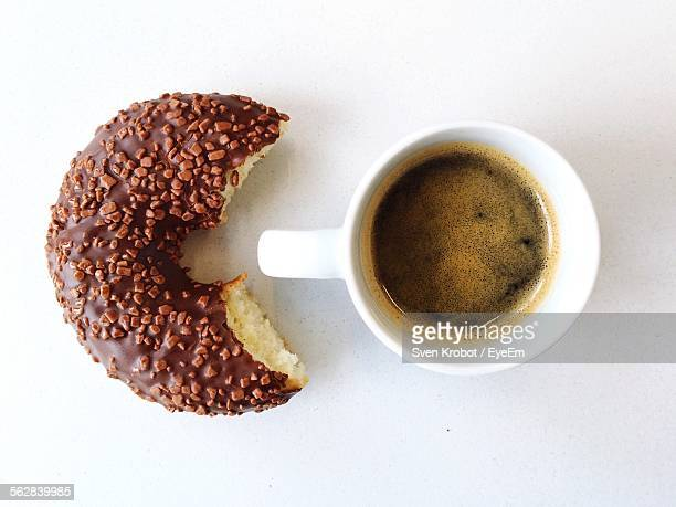 Directly Above Shot Of Coffee And Eaten Donut Against White Background