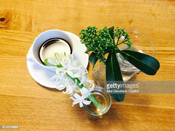 Directly Above Shot Of Coffee And Flowers In Vase On Table