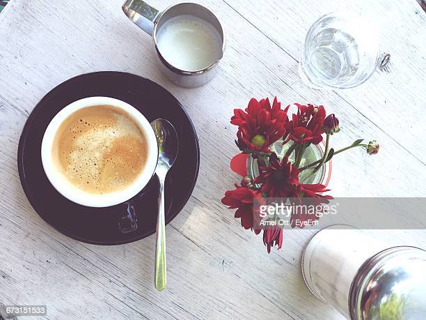 Directly Above Shot Of Coffee And Flowers On Table
