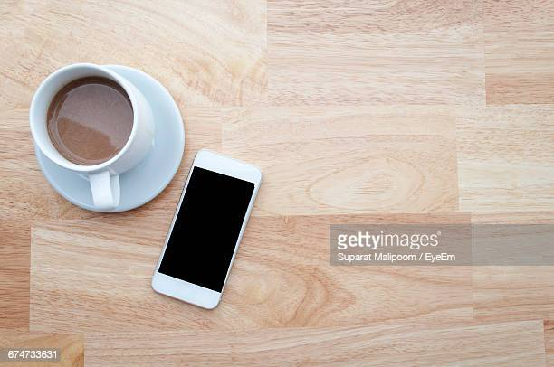 Directly Above Shot Of Coffee And Mobile Phone On Desk