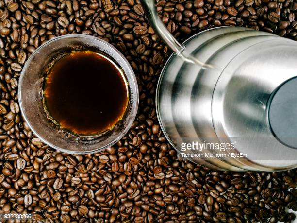 Directly Above Shot Of Coffee By Container On Roasted Beans