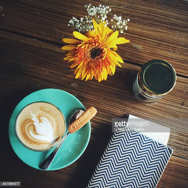 Directly Above Shot Of Coffee By Flower Pot On Table