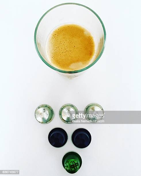 Directly Above Shot Of Coffee Capsules And Drinking Glass Against White Background