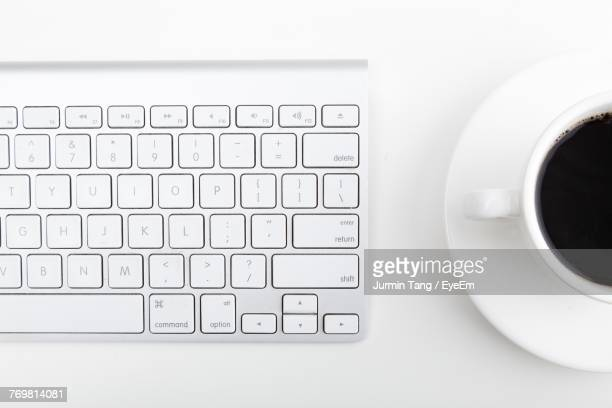 Directly Above Shot Of Coffee Cup And Computer Keyboard On Table