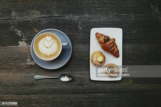 Directly Above Shot Of Coffee Cup And Croissant With Pastries On Wooden Table
