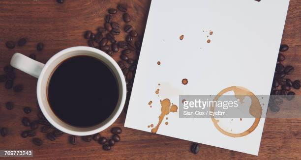 directly above shot of coffee cup and paper on table - stained stock pictures, royalty-free photos & images