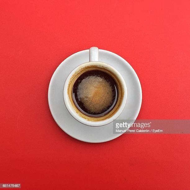 directly above shot of coffee cup on red table - coffee cup stock pictures, royalty-free photos & images