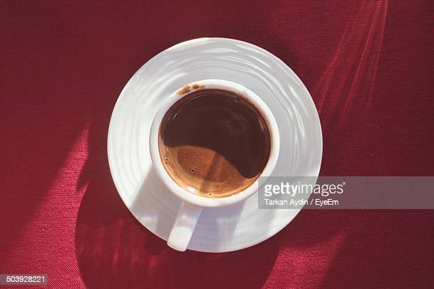Directly above shot of coffee cup on red tablecloth