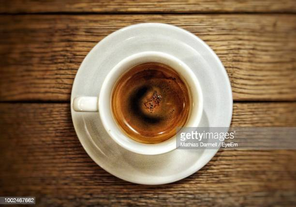 directly above shot of coffee cup on wooden table - espresso stock pictures, royalty-free photos & images