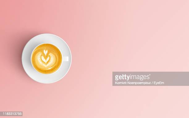 directly above shot of coffee cup over pink background - cappuccino stock pictures, royalty-free photos & images