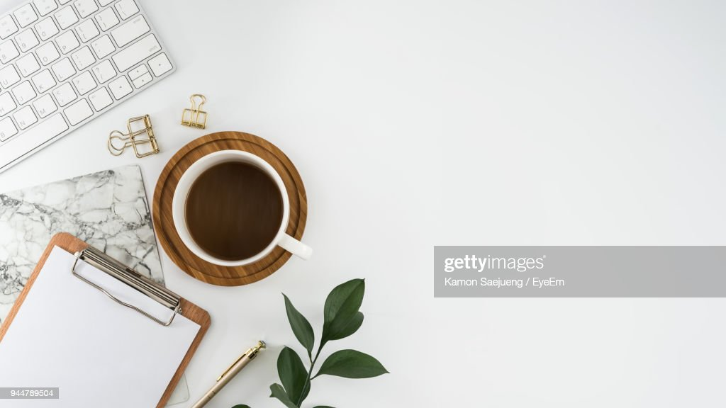 Directly Above Shot Of Coffee Cup With Laptop And Clipboard Over White Background : Stock Photo