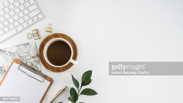 directly above shot of coffee cup with laptop and clipboard over white background - bureau stockfoto's en -beelden