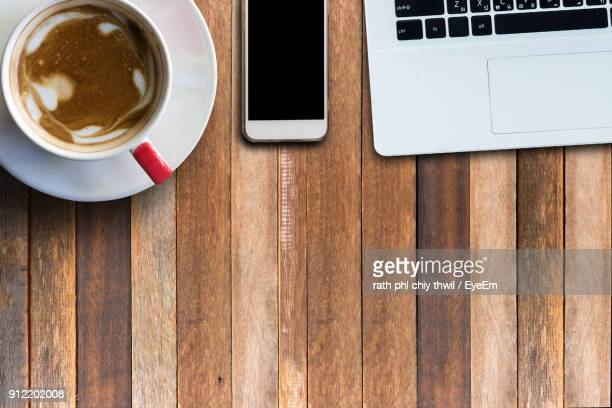 Directly Above Shot Of Coffee Cup With Mobile Phone And Laptop On Table