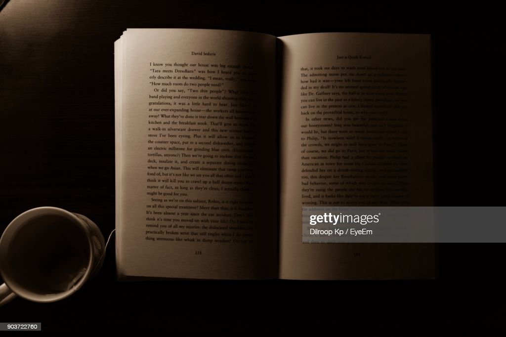 Directly Above Shot Of Coffee Cup With Open Book In Darkroom