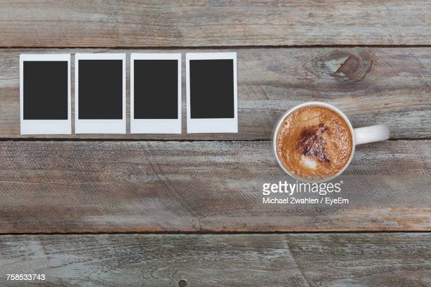 Directly Above Shot Of Coffee Cup With Picture Frames On Table