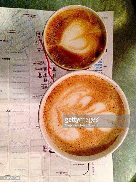 Directly Above Shot Of Coffee Cups On Map At Table