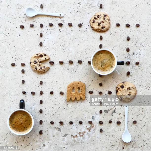 directly above shot of coffee cups with beans and cookies arranged on table - tidy stock pictures, royalty-free photos & images