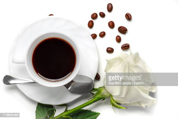 Directly Above Shot Of Coffee In Cup By Rose Flower On White Background