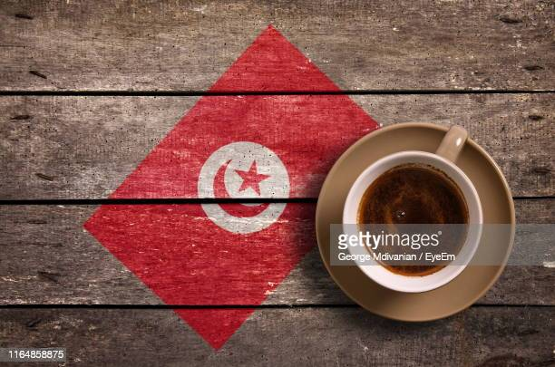 directly above shot of coffee served by national flag painted on wooden table - drapeau tunisien photos et images de collection