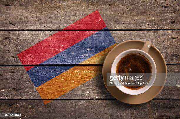 directly above shot of coffee served by national flag painted on wooden table - armenian flag stock pictures, royalty-free photos & images