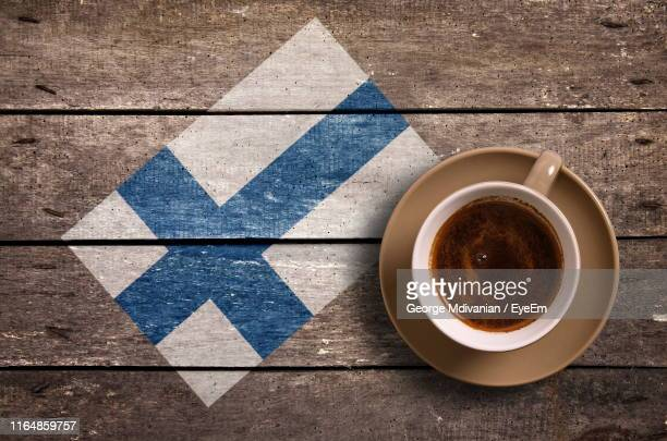 directly above shot of coffee served by national flag painted on wooden table - finsk flagga bildbanksfoton och bilder