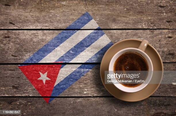 directly above shot of coffee served by national flag painted on wooden table - bandera cubana fotografías e imágenes de stock