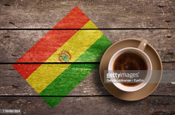 directly above shot of coffee served by national flag painted on wooden table - bandera boliviana fotografías e imágenes de stock