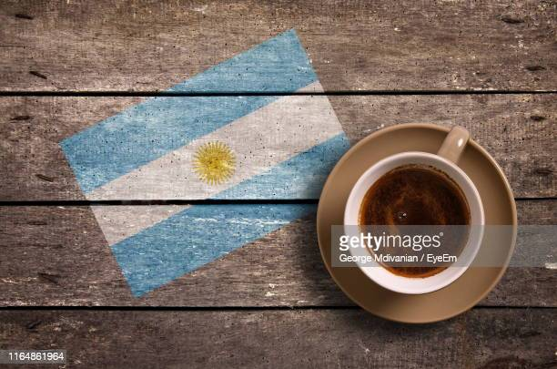 directly above shot of coffee served by national flag painted on wooden table - argentinas flagga bildbanksfoton och bilder