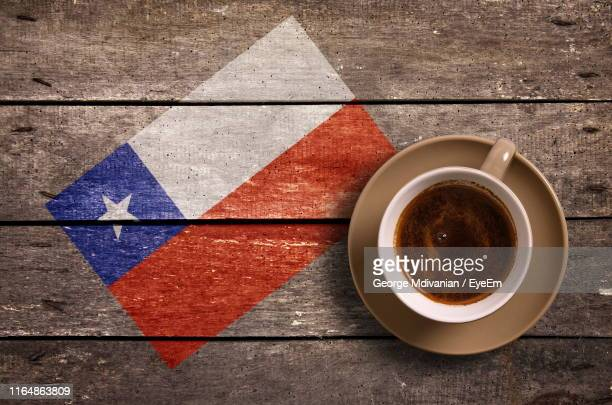 directly above shot of coffee served by national flag painted on wooden table - bandera chilena fotografías e imágenes de stock