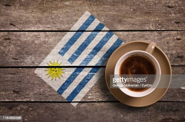 directly above shot of coffee served by national flag painted on wooden table - bandera de uruguay fotografías e imágenes de stock