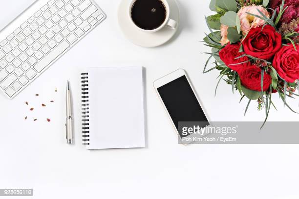 directly above shot of coffee with spiral notebook and mobile phone over white background - kim rose stock-fotos und bilder