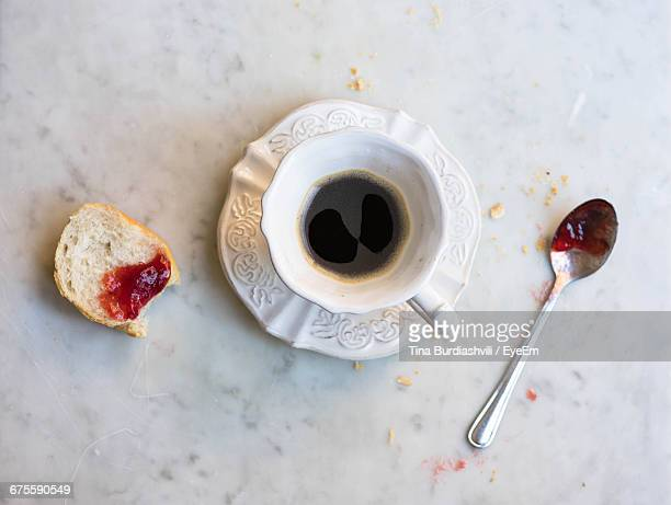 Directly Above Shot Of Coffee With Strawberry Jam On Baguette And Spoon