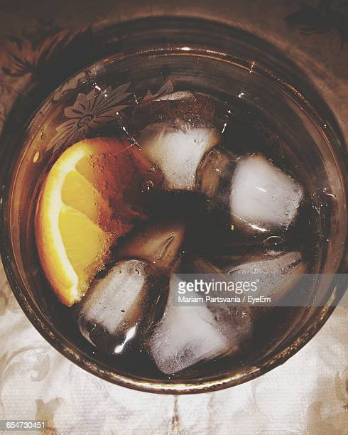 Directly Above Shot Of Cola With Lemon And Ice Cubes In Glass On Table