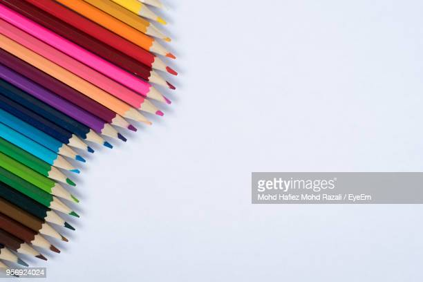 directly above shot of colored pencils over white background - color pencil stock pictures, royalty-free photos & images