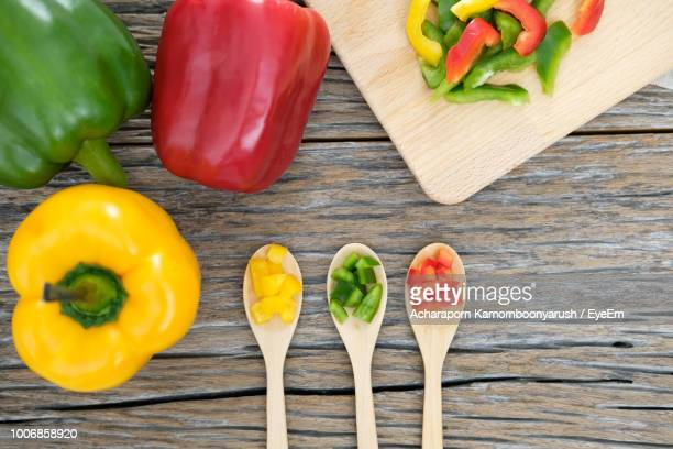 directly above shot of colorful bell peppers on wooden table - pimientos fotografías e imágenes de stock