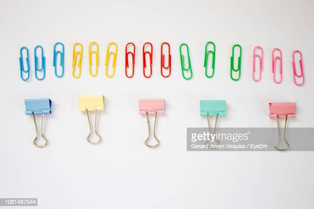 directly above shot of colorful binder and paper clips over white background - binder clip stock pictures, royalty-free photos & images