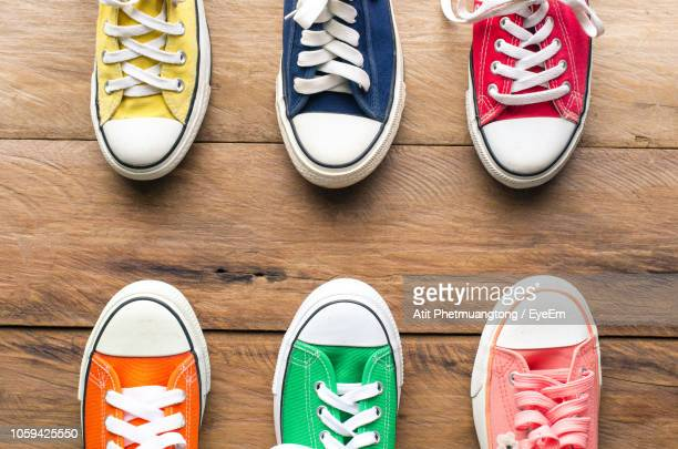 directly above shot of colorful canvas shoes arranged on hardwood floor - multi coloured shoe stock pictures, royalty-free photos & images