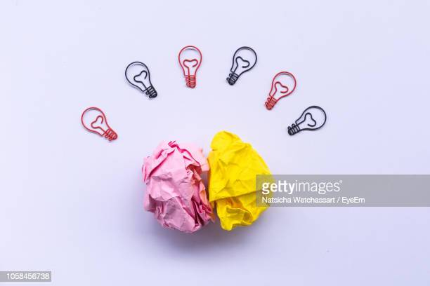 Directly Above Shot Of Colorful Crumpled Papers With Light Bulbs Over White Background
