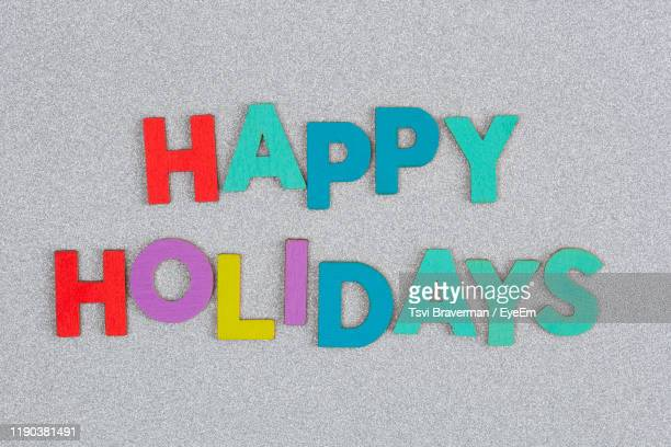 directly above shot of colorful happy holidays text on table - happy holidays stock photos and pictures