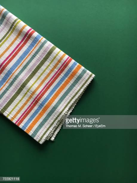 directly above shot of colorful napkin on green background - テーブルナプキン ストックフォトと画像